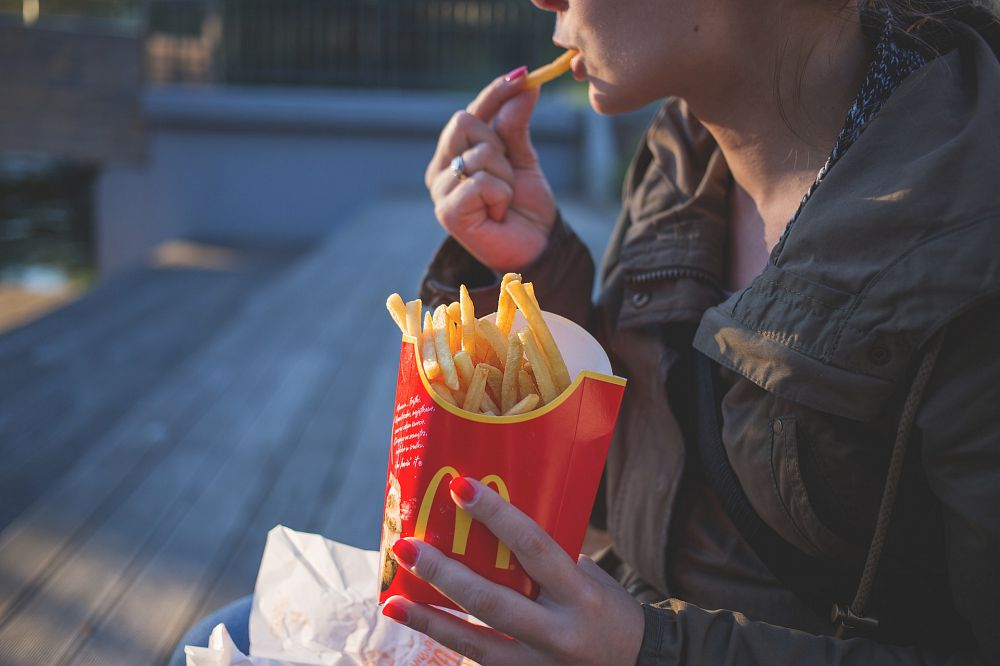 A woman eating fast food french fries